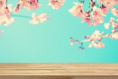 productos naturales: Madera tablero de la mesa en la falta de definición de color rosa Sakura flores de fondo, tono de época - se puede utilizar para la visualización o sus productos Montage