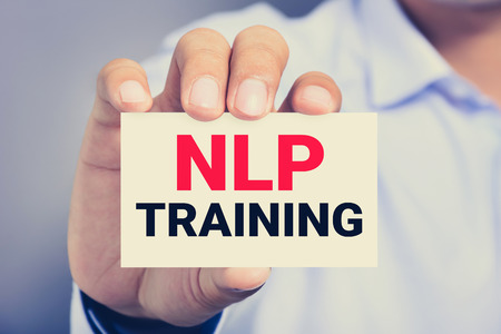 linguistic: NLP TRAINING message on the card shown by a man, NLP stand for Neuro Linguistic Programming