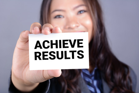 achieve: ACHIEVE RESULTS, message o the card shown by a businesswoman