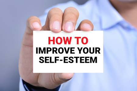 raise your hand: HOW TO IMPROVE YOUR SELF-ESTEEM, message on the card shown by a man