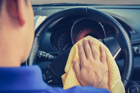 rag wheel: A man cleaning car steering wheel with microfiber cloth, vintage tone image