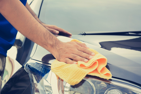 detailing: A man cleaning car with microfiber cloth, vintage tone image