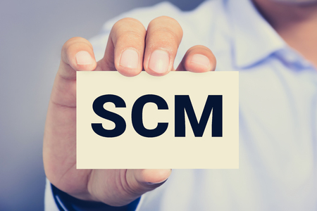 scm: SCM (or Supply Chain Management) letter on the card shown by a man ,vintage tone Stock Photo