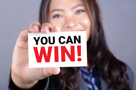 make belief: YOU CAN WIN !, message on the card shown by a businesswoman
