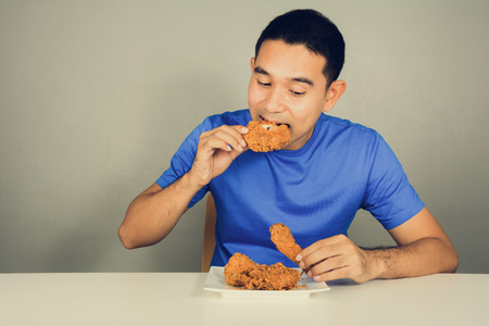 Young man eating fried chicken on the table,  vintage tone