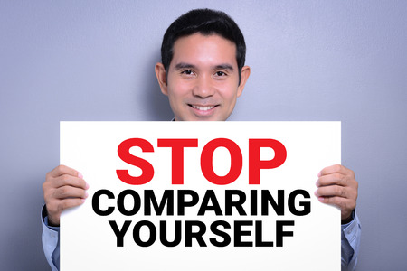 comparing: STOP COMPARING YOURSELF, message on white cardboard held by smiling man