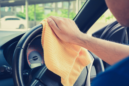 valeting: A man hand cleaning car steering wheel with microfiber cloth, auto detailing (valeting) concept, vintage tone image