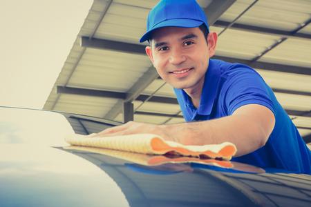 wash: Un hombre de pulido auto con paño de microfibra, detallando el coche o valeting concepto - el rostro enfocado, el tono de la vendimia