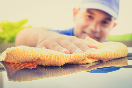 valeting: A man polishing car with microfiber cloth, car detailing (or valeting) concept, vintage tone image Stock Photo