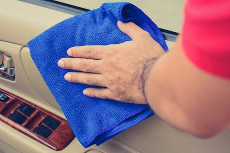 valeting: Hand cleaning interior car door panel with microfiber cloth, vintage tone