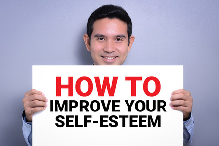 raise your hand: HOW TO IMPROVE YOUR SELF-ESTEEM, message on white cardboard held by smiling man Stock Photo