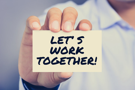 work together: LETS WORK TOGETHER! message on the card shown by a man, vintage tone