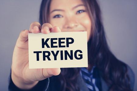 again: KEEP TRYING,message on the card shown by a businesswoman, vintage tone