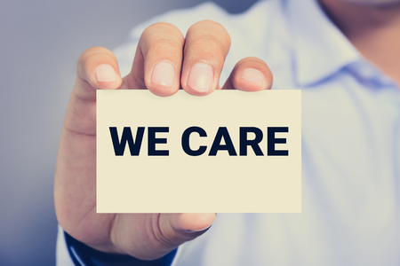 cordiality: WE CARE, message on the card held by a man hand, vintage tone Stock Photo