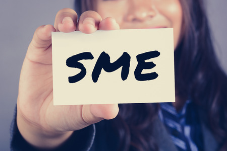 enterprises: SME letters (or Small and Medium-sized  Enterprises) on the card shown by a businesswoman, vintage tone