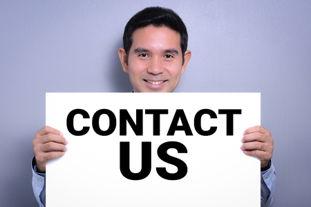 contact us sign: Smiling man showing CONTACT US sign Stock Photo