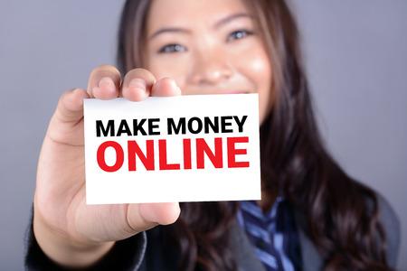 pieniądze: MAKE MONEY ONLINE, message on the card shown by a businesswoman
