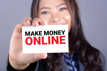 money hand: MAKE MONEY ONLINE, message on the card shown by a businesswoman