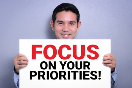 priorities: FOCUS ON YOUR PRIORITIES! message on white cardboard held by smiling man Stock Photo