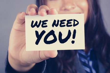 need: WE NEED YOU! message on the card shown by a businesswoman, vintage tone