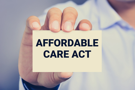 affordable: AFFORDABLE CARE ACT (or ACA) message on the card shown by a man, vintage tone