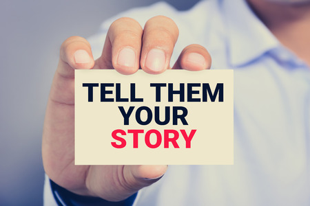 tell: TELL THEM YOUR STORY, message on the card shown by a man, vintage tone