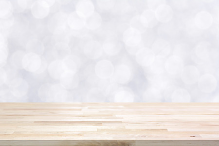 Wood table top on shiny white bokeh abstract background - can be used for display or montage your products