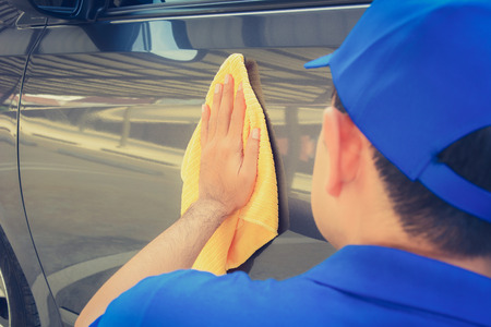 detailing: A man polishing car with microfiber cloth, car detailing (or valeting) concept
