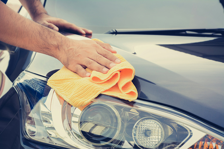 cleaning: A man cleaning car with microfiber cloth, car detailing (or valeting) concept