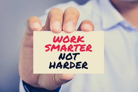 harder: WORK SMARTER NOT HARDER,  motivational text message on the card shown by a man, vintage tone Stock Photo