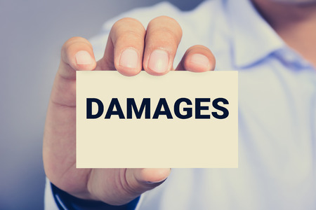 compensate: DAMAGES word on the card shown by a man, vintage tone