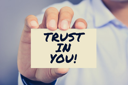 trustworthiness: TRUST IN YOU!, message on the card held by a man hand, vintage tone