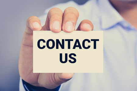 contact: CONTACT US message on the card shown by a man, vintage tone Stock Photo