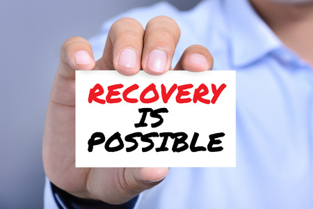 recovery: RECOVERY IS POSSIBLE, message on business card shown by a man Stock Photo