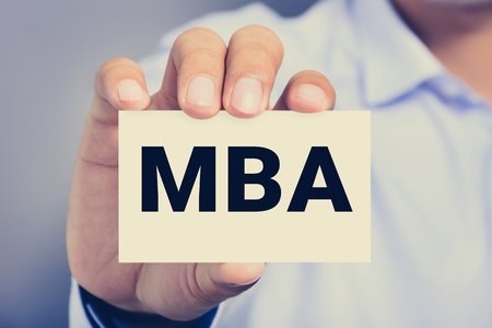 business letters: MBA letters (or Master of Business Administration) on the card held by a man hand, vintage tone