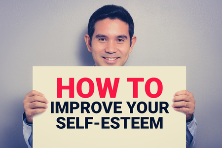 raise your hand: HOW TO IMPROVE YOUR SELF-ESTEEM, message on white cardboard held by smiling man, vintage tone Stock Photo