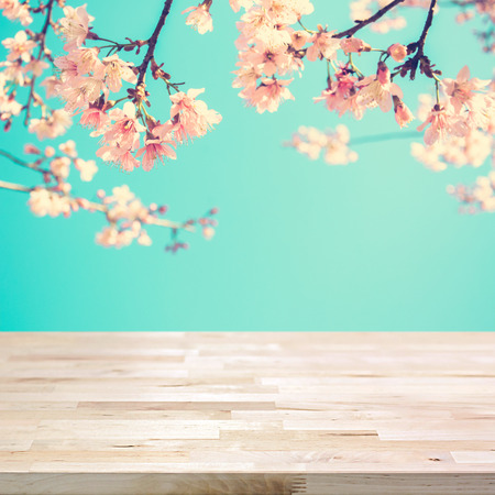 Wood table top on blur pink Sakura flower background- can be used for display or montage your products Imagens