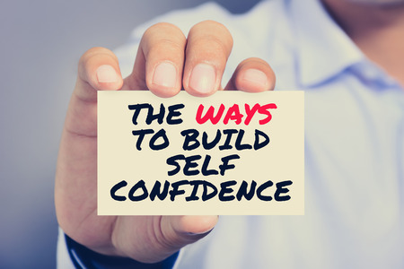 Self Confidence: THE WAYS TO BUILD SELF CONFIDENCE, message on the card shown by a man, vintage tone