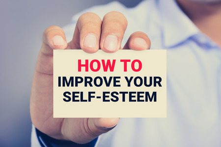 raise your hand: HOW TO IMPROVE YOUR SELF-ESTEEM, message on the card shown by a man, vintage tone Stock Photo