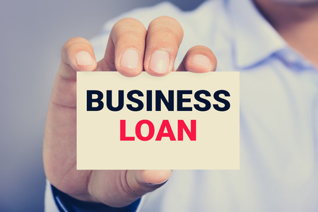 lend a hand: BUSINESS LOAN message on the card shown by a man, vintage tone Stock Photo