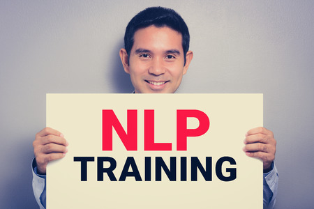 training programs: NLP TRAINING, message on white cardboard held by smiling man, vintage tone Stock Photo