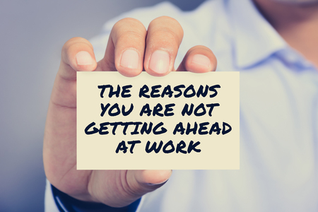 reason: THE REASON YOU ARE NOT GETTING AHEAD AT WORK, message on the card shown by a man Stock Photo