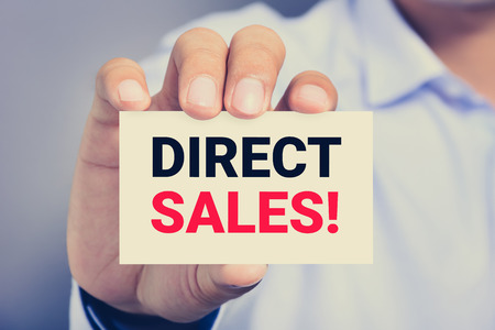 hard sell: DIRECT SALES! message on the card shown by a man, vintage tone
