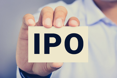 public market sign: IPO letters  (or Initial Public Offering) on the card held by a man hand, vintage tone