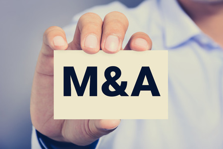 company ownership: M & A letters (or Merger and Acquisition) on the card held by a man hand, vintage tone Stock Photo