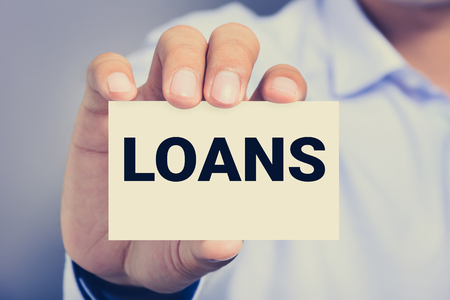 loans: LOANS word on the card shown by a man, vintage tone Stock Photo