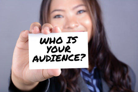 audience: Businesswoman showing card with WHO IS YOUR AUDIENCE ? meaasge