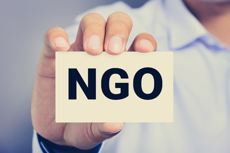 ngo: NGO letters (or Non-Governmental Organization) on the card shown by a man, vintage tone Stock Photo