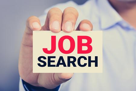job: BÚSQUEDA DE EMPLEO, mensaje en la tarjeta mostrada por un hombre, el tono de la vendimia