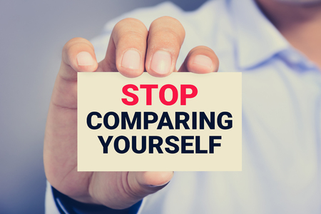 card stop: STOP COMPARING YOURSELF, message on the card shown by a man, vintage tone Stock Photo